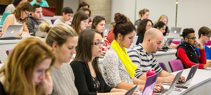Étudiants dans une salle de classe prennent des notes à l'ordinateur.